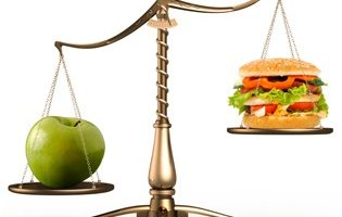 Big green ripe apple and junk food hamburger on scales isolated white background
